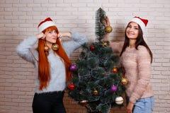 Dos mujeres jovenes hermosas en Papá Noel capsulan el adornamiento del tre de la Navidad Fotografía de archivo