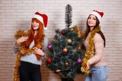 Dos mujeres jovenes hermosas en Papá Noel capsulan el adornamiento del tre de la Navidad Imagenes de archivo