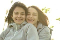 Dos mujeres jovenes hermosas que abrazan y que ríen Imágenes de archivo libres de regalías