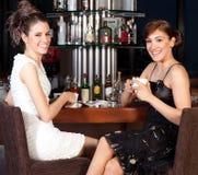 Dos mujeres jovenes hermosas que beben el café en la barra Imágenes de archivo libres de regalías