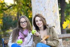 Dos mujeres jovenes hermosas que celebran manzanas verdes y la sonrisa Imagenes de archivo