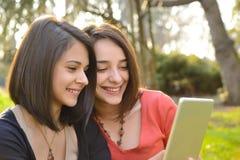 Dos mujeres jovenes hermosas que hojean una tableta Imágenes de archivo libres de regalías