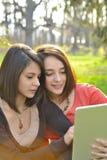 Dos mujeres jovenes hermosas que hojean una tableta Imagenes de archivo