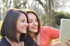 Dos mujeres jovenes hermosas que hojean una tableta Foto de archivo