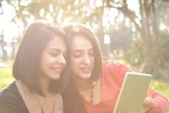 Dos mujeres jovenes hermosas que hojean una tableta fotografía de archivo