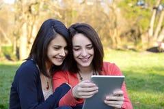 Dos mujeres jovenes hermosas que hojean una tableta Foto de archivo libre de regalías