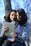 Dos mujeres jovenes hermosas que hojean una tableta afuera Imagen de archivo libre de regalías
