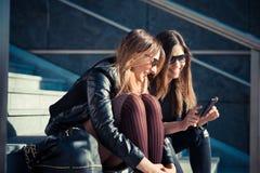 Dos mujeres jovenes hermosas que usan el teléfono elegante fotografía de archivo libre de regalías