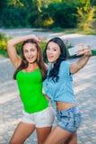 Dos mujeres jovenes hermosas que usan el teléfono elegante para Imagen de archivo libre de regalías