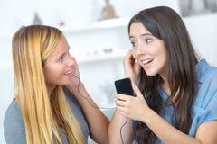 Dos mujeres jovenes hermosas sonrientes con los auriculares que escuchan la música Foto de archivo libre de regalías