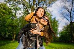 Dos mujeres jovenes lindas pasan alegre tiempo en el parque de la primavera Foto de archivo