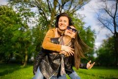 Dos mujeres jovenes lindas pasan alegre tiempo en el parque de la primavera Fotografía de archivo