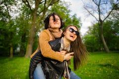 Dos mujeres jovenes lindas pasan alegre tiempo en el parque de la primavera Foto de archivo libre de regalías