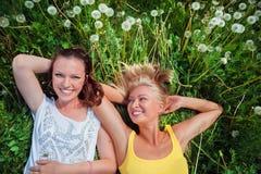 Dos mujeres jovenes lindas que mienten en la hierba en outd del día soleado del verano Imagen de archivo libre de regalías