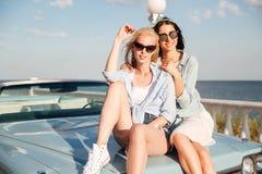 Dos mujeres jovenes magníficas que se sientan en el coche fotos de archivo libres de regalías