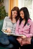 Dos mujeres jovenes mientras que hace compras en el catálogo Imagen de archivo libre de regalías
