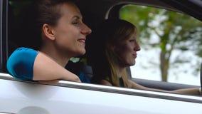 Dos mujeres jovenes montan en un coche y se divierten almacen de metraje de vídeo