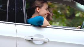Dos mujeres jovenes montan en un coche y se divierten Cámara lenta almacen de video