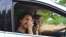 Dos mujeres jovenes montan en un coche y se divierten Uno de ellos toma una foto del uno mismo en una cámara de la película Cámar metrajes