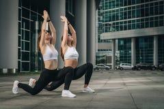 Dos mujeres jovenes, muchachas que hacen estirando los ejercicios, calentamiento, haciendo yoga en la calle de la ciudad Entrenam imágenes de archivo libres de regalías