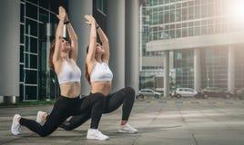 Dos mujeres jovenes, muchachas que hacen estirando los ejercicios, calentamiento, haciendo yoga en la calle de la ciudad Entrenam imagenes de archivo