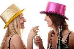 Dos mujeres jovenes ocasionales que gozan del champán Foto de archivo