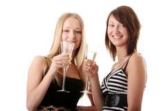 Dos mujeres jovenes ocasionales que gozan del champán Fotos de archivo libres de regalías