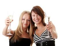 Dos mujeres jovenes ocasionales que gozan del champán Imagen de archivo libre de regalías