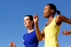 Dos mujeres jovenes que activan contra el cielo azul Fotografía de archivo
