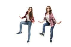 Dos mujeres jovenes que bailan sobre el fondo blanco fotografía de archivo libre de regalías