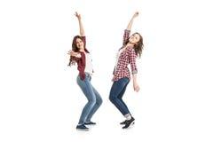 Dos mujeres jovenes que bailan sobre el fondo blanco foto de archivo
