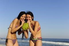 Dos mujeres jovenes que beben el agua del coco Imagen de archivo