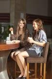 Dos mujeres jovenes que beben el café en una barra Fotos de archivo libres de regalías