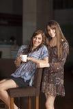 Dos mujeres jovenes que beben el café en una barra Imagenes de archivo