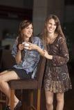 Dos mujeres jovenes que beben el café en una barra Foto de archivo libre de regalías