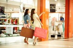 Dos mujeres jovenes que caminan con compras en la tienda Imágenes de archivo libres de regalías