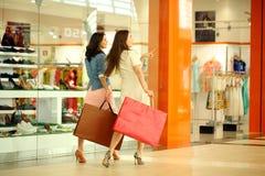 Dos mujeres jovenes que caminan con compras en la tienda Imagen de archivo