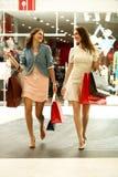 Dos mujeres jovenes que caminan con compras en la tienda Imagen de archivo libre de regalías
