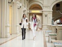 Dos mujeres jovenes que caminan con compras en la tienda Fotos de archivo libres de regalías