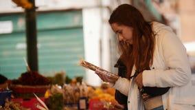 Dos mujeres jovenes que caminan en el mercado exterior y que buscan los dulces exóticos almacen de metraje de vídeo