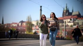 Dos mujeres jovenes que caminan en las calles de Praga almacen de metraje de vídeo