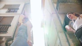 Dos mujeres jovenes que caminan más allá de edificios a través del callejón metrajes