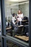 Dos mujeres jovenes que conversan en laboratorio del ordenador Foto de archivo