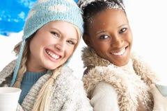 Dos mujeres jovenes que desgastan la ropa del invierno en estudio Imágenes de archivo libres de regalías