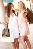 Dos mujeres jovenes que disfrutan de viaje de las compras Fotografía de archivo libre de regalías