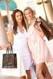 Dos mujeres jovenes que disfrutan de viaje de las compras Imágenes de archivo libres de regalías
