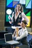 Dos mujeres jovenes que encuentran con las computadoras portátiles en el vector Foto de archivo libre de regalías