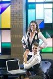 Dos mujeres jovenes que encuentran con las computadoras portátiles en el vector Imágenes de archivo libres de regalías