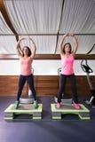 Dos mujeres jovenes que estiran el gimnasio de pasos Fotografía de archivo