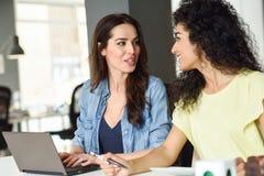 Dos mujeres jovenes que estudian con un ordenador portátil Fotografía de archivo libre de regalías
